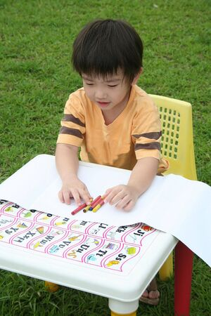 happily: Boy happily coloring with crayon
