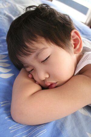 enfant qui dort: Petit gar�on dort sur ses bras