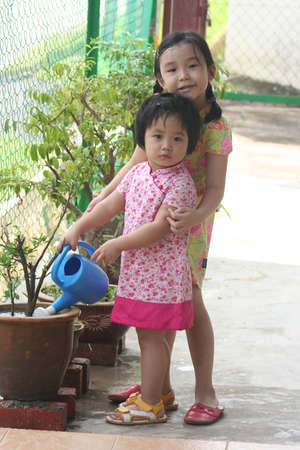 wateringcan: Girls holding watering-can watering plant