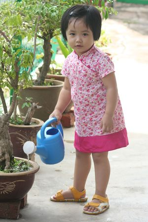 wateringcan: Girl holding watering-can watering plant