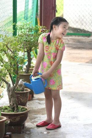 wateringcan: Girl holding watering-can watering the plant Stock Photo