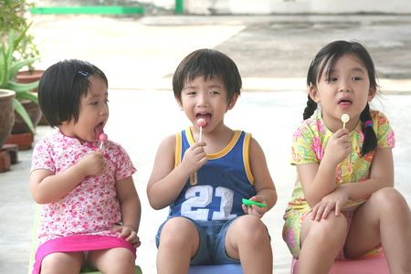 lolly pop: Kids sitting & enjoying lolly pop