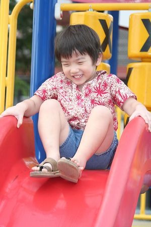 Little happy boy playing on slide photo