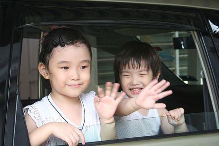 Muchacho y muchacha que agitan adiós en el coche Foto de archivo - 574128