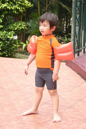 swimming costume: Little boy wearing swimming costume, standing bare-footed