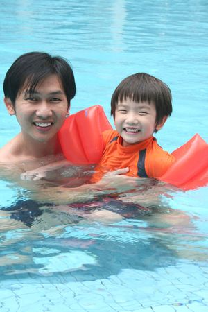 Man & little boy swimming in the pool photo