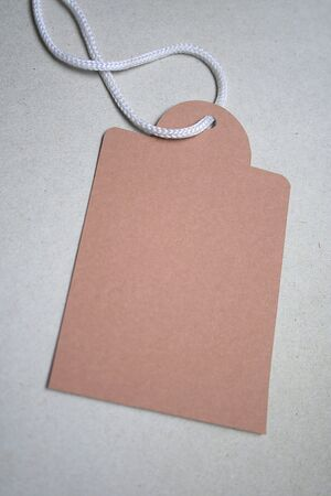 Brown tag with white string on grey card board Reklamní fotografie
