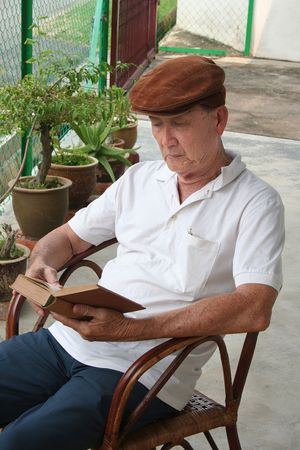 Old man sitting on the chair reading a book Stock Photo - 668076