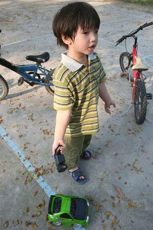 ni�os en recreo: Boy jugando verde control remoto coche en el parque infantil
