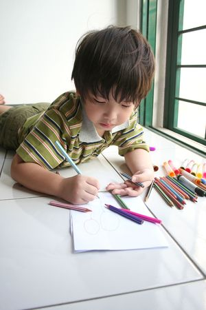 Boy lying on the floor and drawing on the paper photo