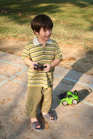 Boy playing green remote control car at the children playground photo