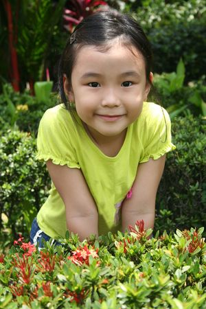 standing alone: Little girl smiling and standing alone in the garden Stock Photo