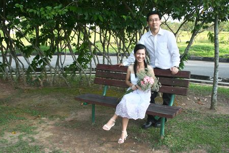 Wedding couple sitting on the bench in the park photo