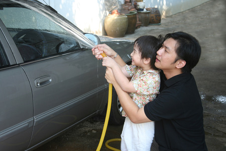 Man and kid washing car in a sunny afternoon happily photo