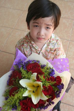 Little boy holding bouquet of red roses and lily Stock Photo - 2056423