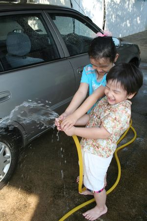 Kids washing car in a sunny afternoon happily photo