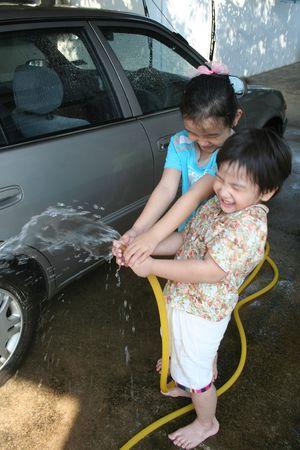 auto lavado: Ni�os de lavado de autom�viles en una soleada tarde feliz  Foto de archivo