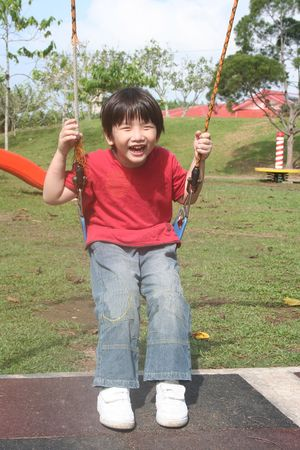Happy boy swinging happily at the playground in the park photo
