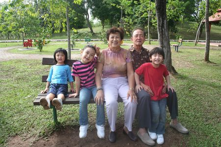 generation gap: Grandparents and grandchildren having fun in the park