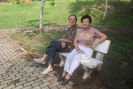 Senior couple sitting on the bench in the park photo