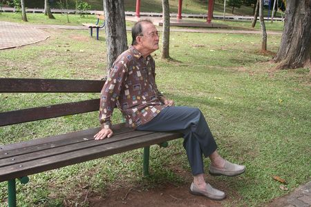 Senior man sitting on the bench in the park photo