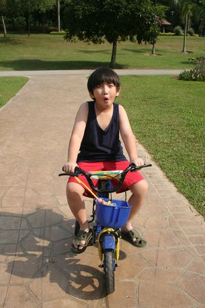 Happy boy cycling at the park in the afternoon photo
