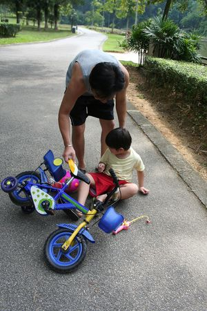 levantandose: Padre ayuda a hijo de levantarse de la ca�da de bicicleta