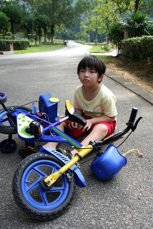 Little boy falling off bicycle sitting on the floor photo