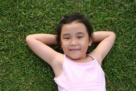 singlet: Girl wearing pink singlet lying on the grass Stock Photo