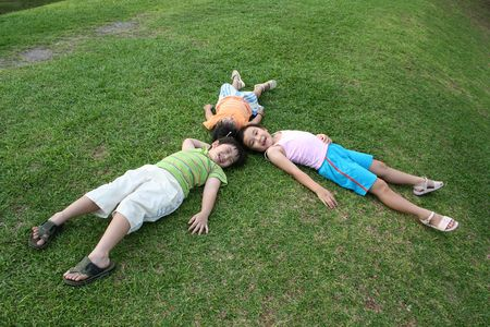 outdoor activities: Happy girls and boy lying on the grass