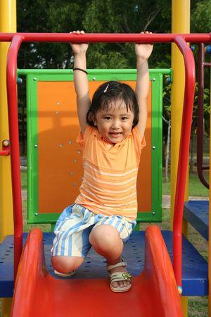 squatting: Chica usar tee naranja en las diapositivas en el parque