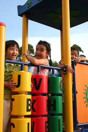Two girls and one boy playing at the park Stock Photo