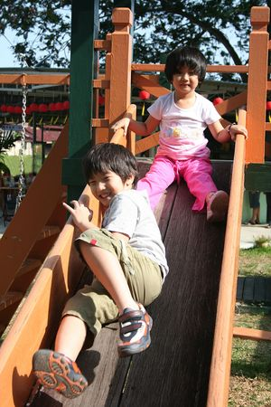 playground children: Happy children playing slide at the playground in the park on sunny day