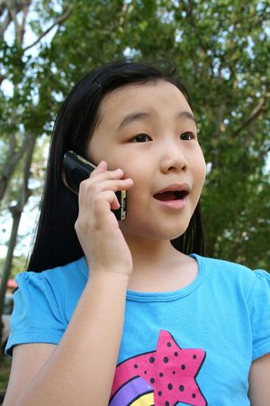 telecommute: Girl talking on mobile phone in the park