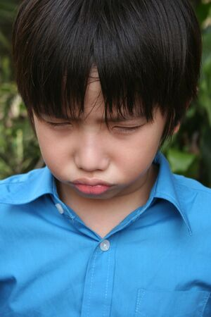 Little boy in blue shirt showing angry face in the park Stock Photo - 4358646