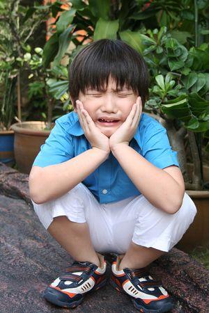 squatting: Triste muchacho en cuclillas y la celebraci�n de su cara en el parque