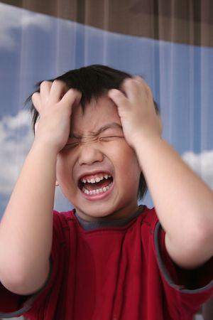 ni�os malos: Enojado muchacho t� rojo en la celebraci�n de su cabeza gritando airadamente