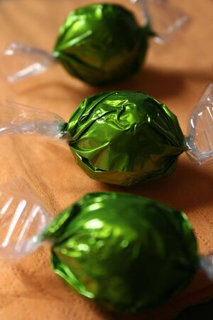 obesity kids: Candies wrapped with green wrappers placed on orange table mat