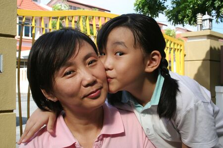 Happy daughter hugging and kissing mother on the cheek photo