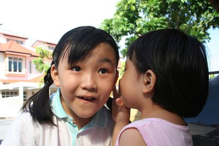 Little girl in pink telling another girl a secret photo
