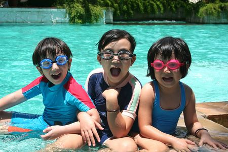 kid sitting: Kids with goggles in the pool on sunny day