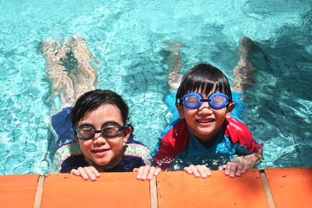 child sport: Kids with goggles in the pool on sunny day