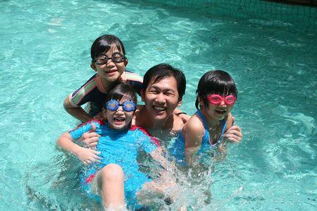 attivit?: Padre e bambini che giocano felici in piscina