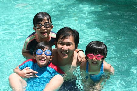 swim goggles: Father and children playing happily in the pool
