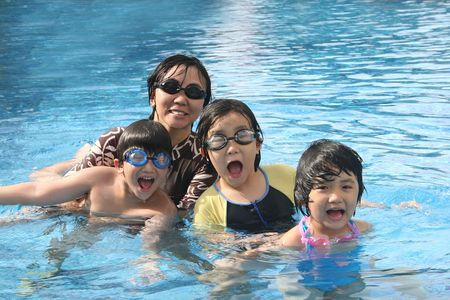 Mother and kids playing happily in the pool Stock Photo - 6283664