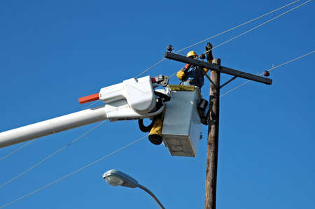 A picture of a man in a bucket lift repairing a power line