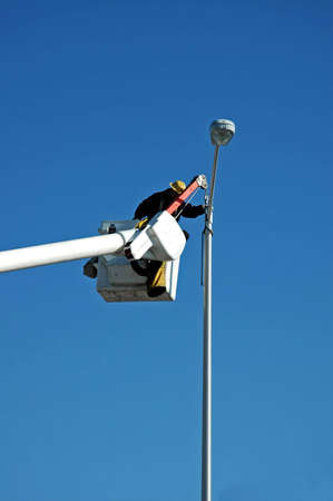 A picture of a man on a bucket lift working on a street light Stock Photo