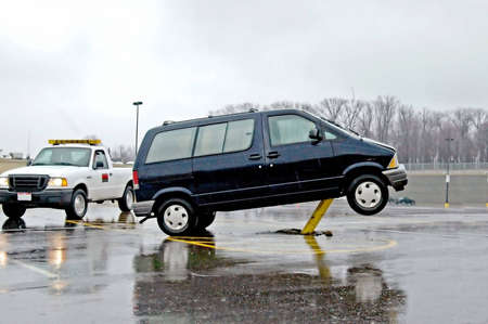 A picture of a wrecked car sitting on a pole in a parking lot