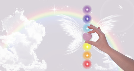 discernment: Hand holding Rose Quartz heart and The Seven Chakras