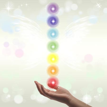 Healing Hands and seven chakras on a sparklingpastel coloured background Archivio Fotografico